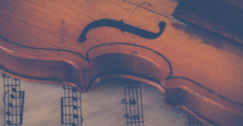 A violin resting on a sheet of music. Photo: Ylanite Koppens/Pexels
